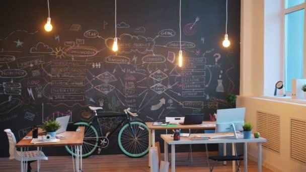 Krásná kancelář ve stylu podkroví s dřevěnou stěnou a moderním nábytkem a světly