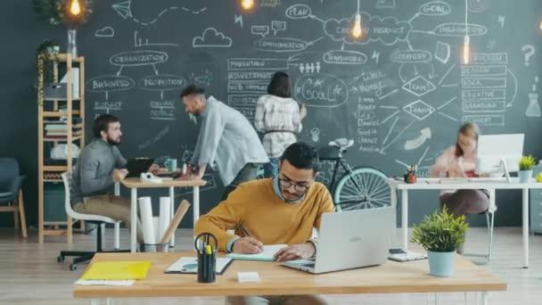 Zoom-Zeitraffer eines arabischen Mannes, der im gemeinsamen Büro arbeitet und mit Laptop schreibt und tippt