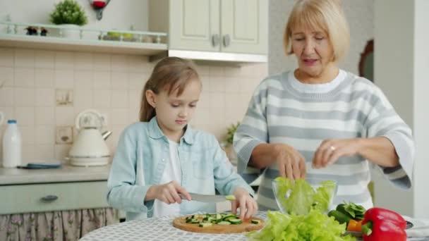 Nagymama és aranyos gyerek főzés saláta ebédre beszél, hogy egészséges étel otthon