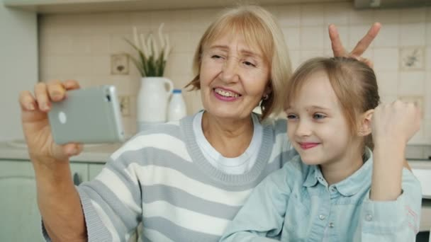 Joyful granny and little girl taking selfie with smartphone camera in cozy modern kitchen
