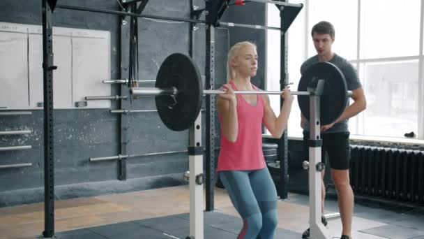 Slender sportswoman in sportswear squatting with barbell working out with coach in gym