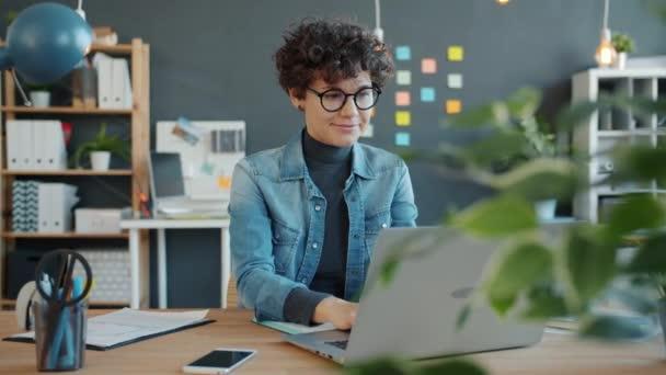 Zeitlupe einer jungen Geschäftsfrau, die im kreativen Büro mit einem Laptop arbeitet