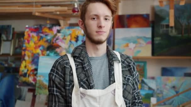 Zeitlupe Porträt eines hübschen jungen Mannes Kunststudent in modernem Malatelier