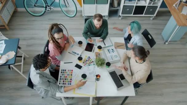 Blick aus der Vogelperspektive auf junge Leute, die im Büro reden und Kaffee trinken