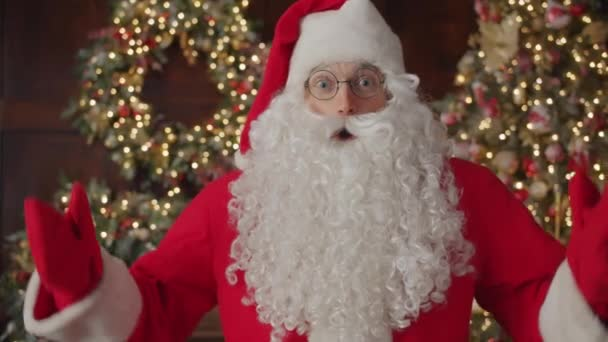 Portrét muže v kostýmu Santa Clause a brýle při pohledu do kamery u vánočního stromku