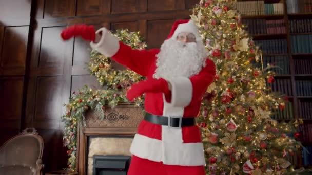 Portrét veselého Santa Clause, jak se baví tancováním ve zdobeném domě v červeném kostýmu