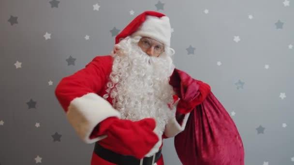 Guy v Santa oblečení držení taška s dárky mrkání při pohledu na kameru na hvězdném pozadí