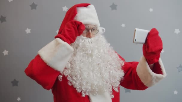 Portrait of Santa Claus taking selfie with smartphone camera on grey glittery background
