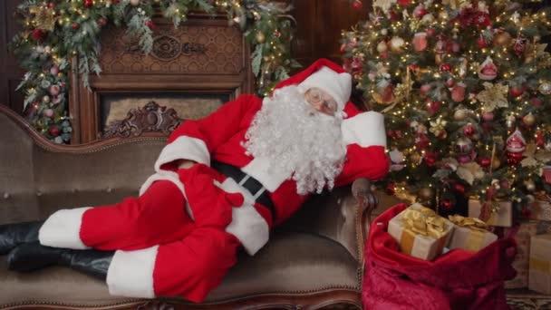 Santa Claus spí ve zdobeném pokoji v blízkosti vánočního stromečku s taškou dárků
