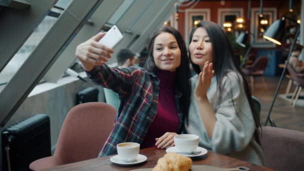 Barátok lányok csinál szelfi a kávézóban gazdaság smartphone ül az asztalnál, szórakozás nevetés