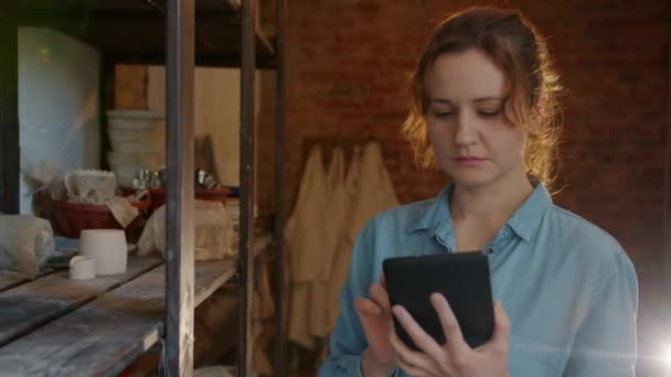 Slow motion of serious girl using tablet in pottery workshop looking at ceramics