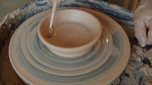 Bezešvé smyčka keramické mísy rotující na hrnčířském kole a keramici ruku zdobení