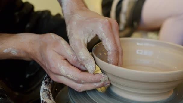 Close-up der Jungs Hände Herstellung Schale mit Ton auf Töpferscheibe in der Werkstatt