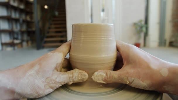 Detailní záběr špinavých rukou tvarování hlíny do misky na hrnčířském kole pracuje uvnitř