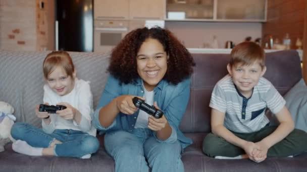 Gyors mozgás izgatott gyermekek és a dada élvezi videojáték szórakozás és nevetés otthon