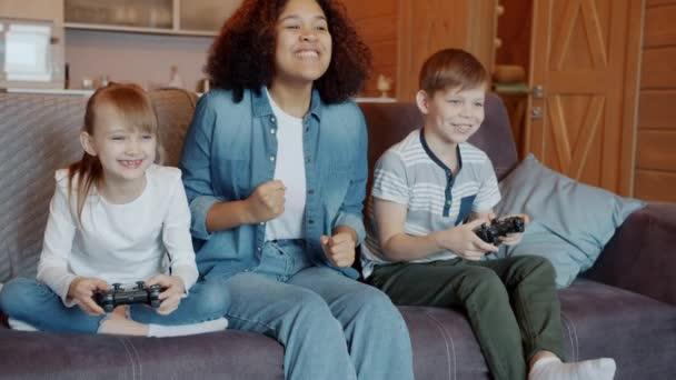 Boldog gyerekek fiú és lány videojáték, míg a bébiszitter éljenzés otthon