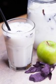 Ayran - liquid drink made from yogurt in ransparent glass cup and green apple