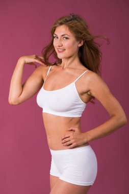 Young beautiful blonde woman in white fitness clothing, isolated on plum background