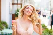Portrét krásné sexy Mladá blondýnka s dlouhými kudrnatými vlasy, jíst chutné zmrzliny