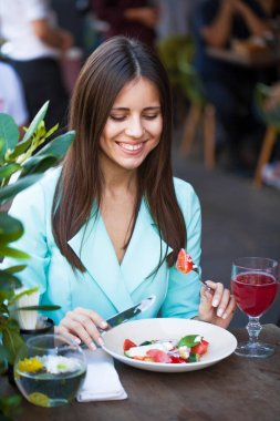 Young beautiful brunette woman is having breakfast in a cafe, summer street outdoors