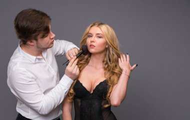 Stylist and his blonde model posing in the studio on a gray background