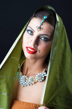 Fashion portrait of pretty sexy young brunette woman in green sari posing on dark studio background