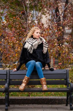 Portrait of a full length young blonde woman in mink winter fur coat sitting on a bench, outdoors in autumn street
