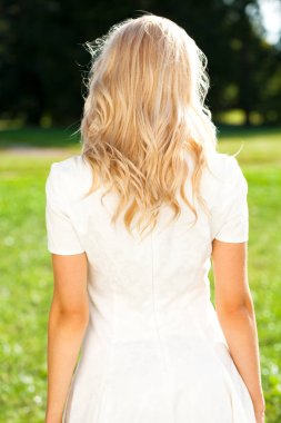 Female Long wavy blonde hair, rear view, summer street outdoors