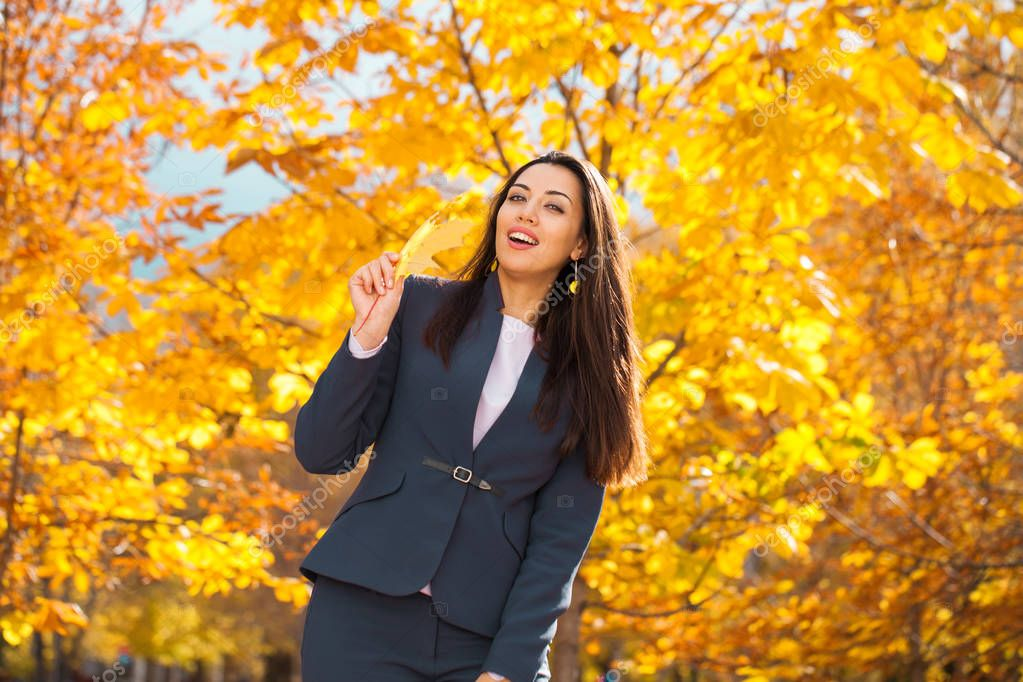 Happy successful arab businesswoman in blue suit walking in autumn park
