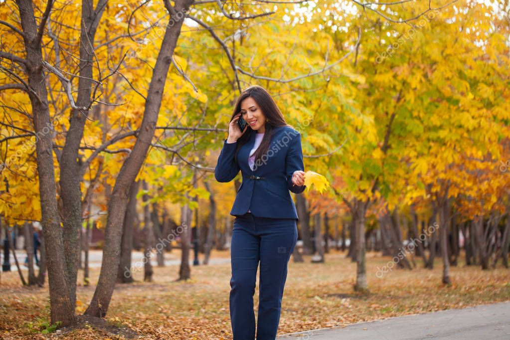 Woman calling by phone. Happy successful arab businesswoman in blue suit walking in autumn park
