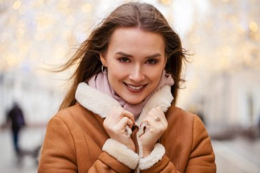 Happy Beautiful woman in a sheepskin coat in the center of the C