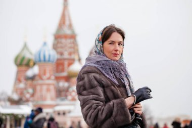 Young woman in fur mink coat on a red square in the center of Mo