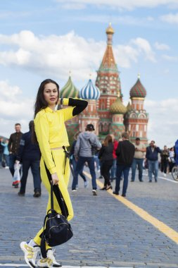 Portrait of a young beautiful brunette woman in yellow tracksuit