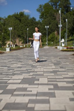 Young beautiful brunette girl in white jeans and t-shirt walking