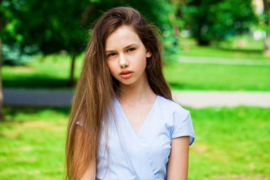 Close up portrait of a young beautiful brunette  girl in summer park