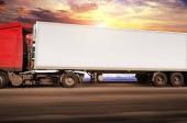 Camion rosso e bianco rimorchio con spazio per il testo di guida veloce su strada della campagna contro il cielo con il tramonto