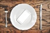 Bílý smartphone s velké bílé plátno na desce s stříbrným nožem a vidličkou na tmavé dřevěné pozadí