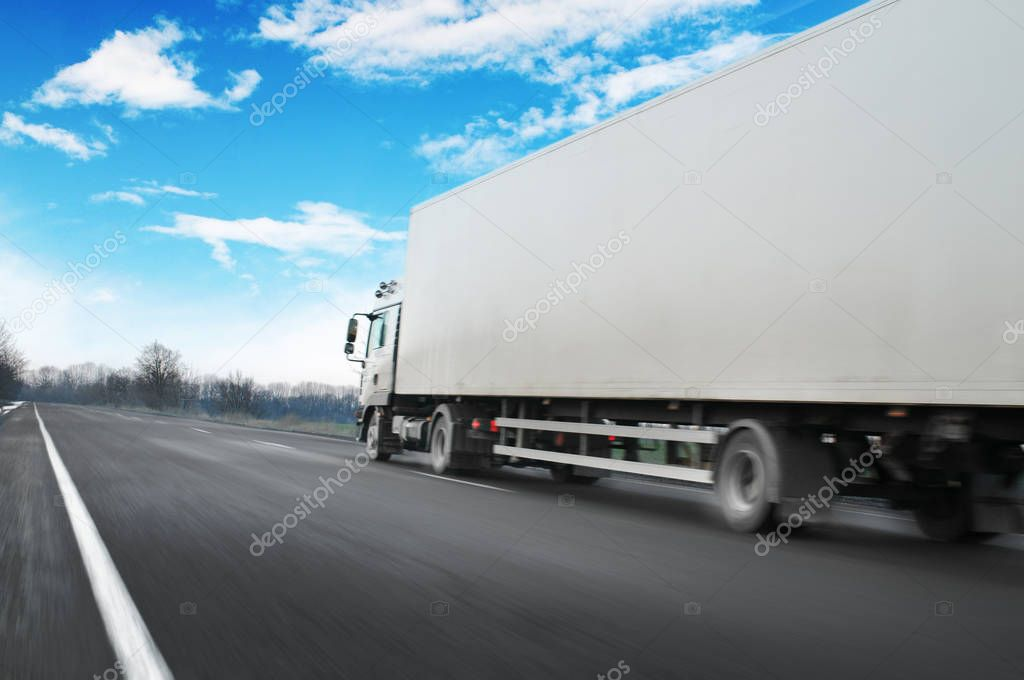 White truck driving fast with space for text on countryside road against blue sky with clouds