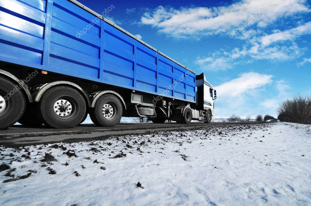 White truck and blue trailer with space for text on winter countryside road with snow against blue sky with clouds