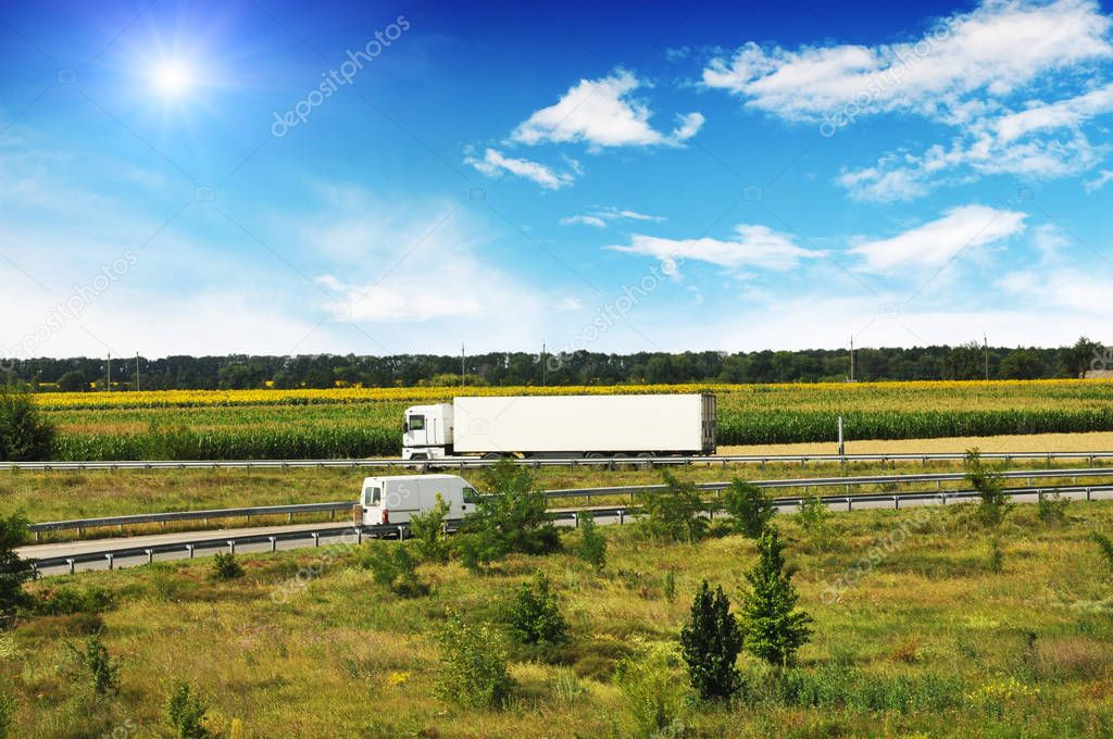 White truck with white trailer and van on countryside road with fields and forest against blue sky with clouds and sun