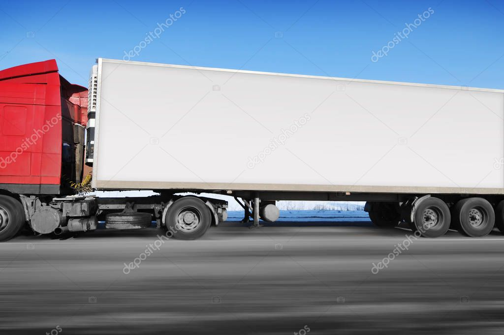 Red truck and white trailer with space for text driving fast on winter countryside road with snow against blue sky