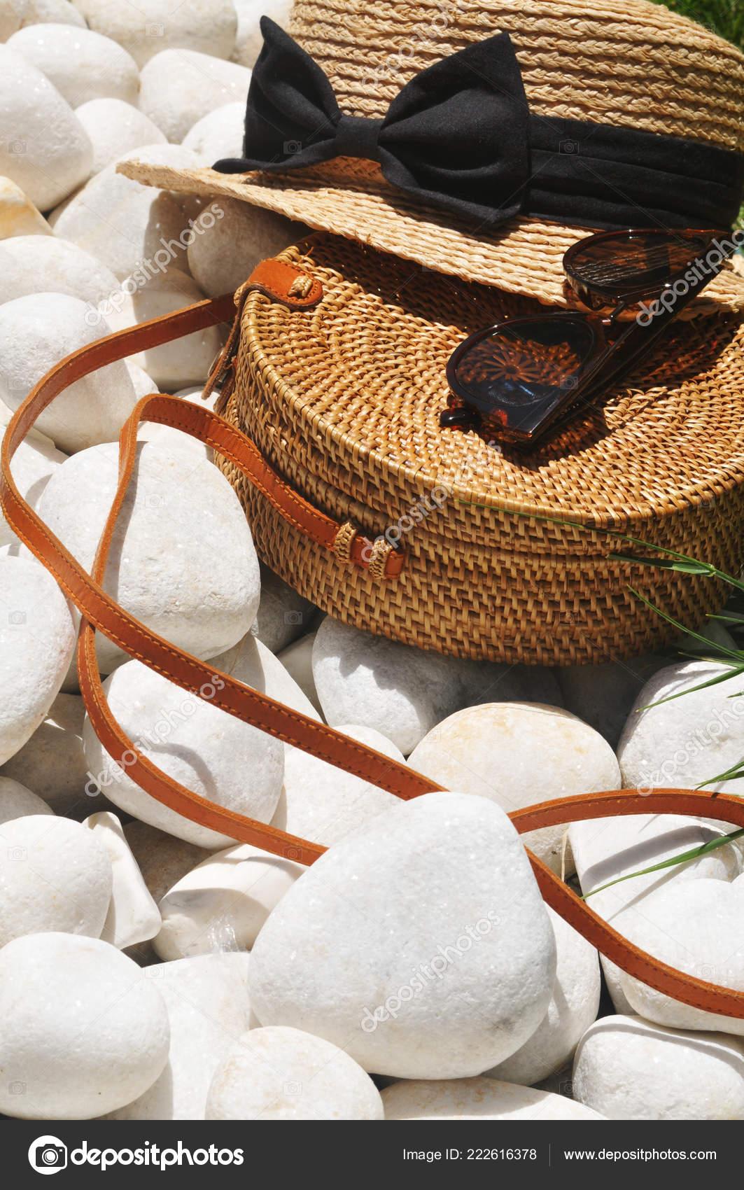 Bolso de paja redondo y sombrero de paja con negro gafas de sol en las  piedras del guijarro — Foto de jonson 4a276b3ec76
