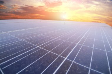 Close-up of large solar panel against sky with sunset