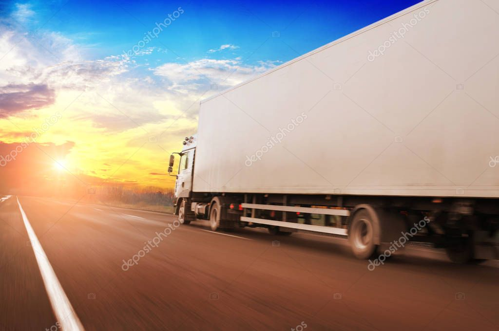 White truck driving fast and white trailer with space for text on countryside road against blue sky with bright sunset