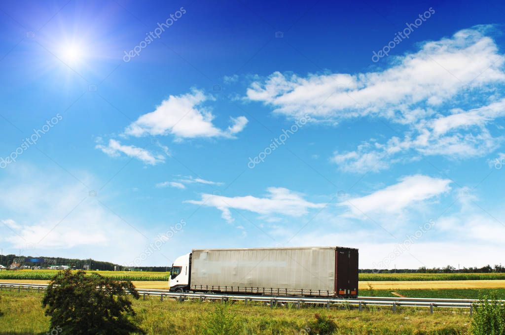 Blue truck with trailer on countryside road with fields and green trees against blue sky with clouds and sun
