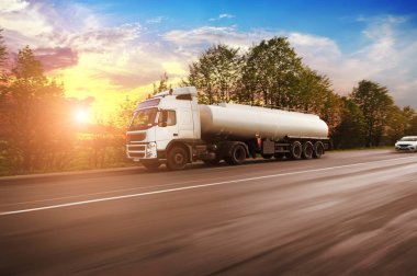 Big metal fuel tanker truck shipping fuel on countryside road in motion with trees against sky with sunset