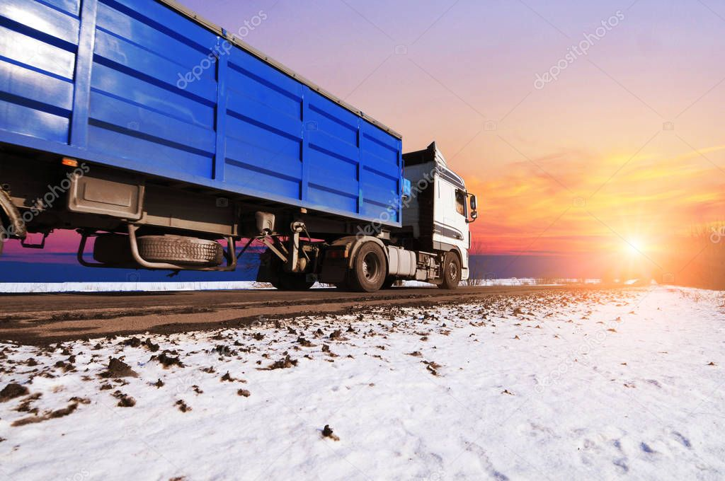 White truck and blue trailer driving fast on winter countryside road with snow against sky with sunset
