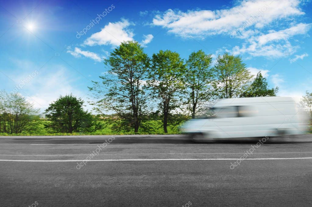 Blurred white big van driving fast on countryside road with green trees and bushes against blue sky with clouds