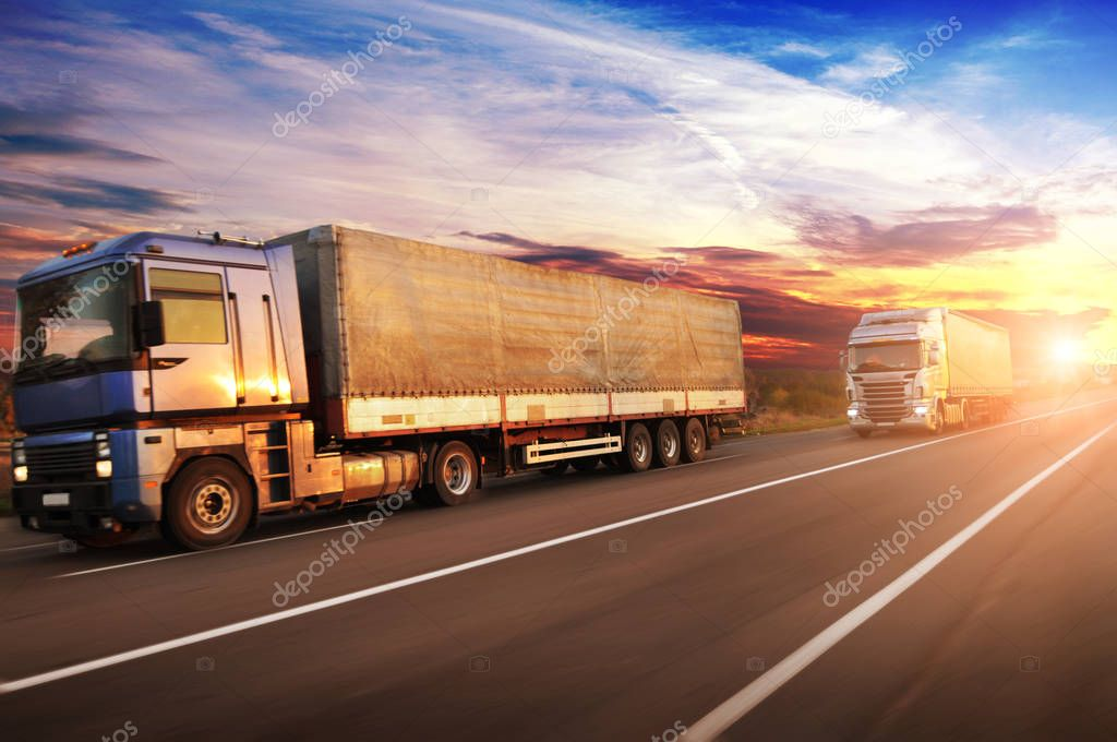 Big trucks in motion with space for text on countryside road against sky with sunset