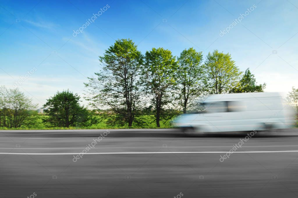 White big van driving fast on countryside road in motion with green trees and bushes against blue sky